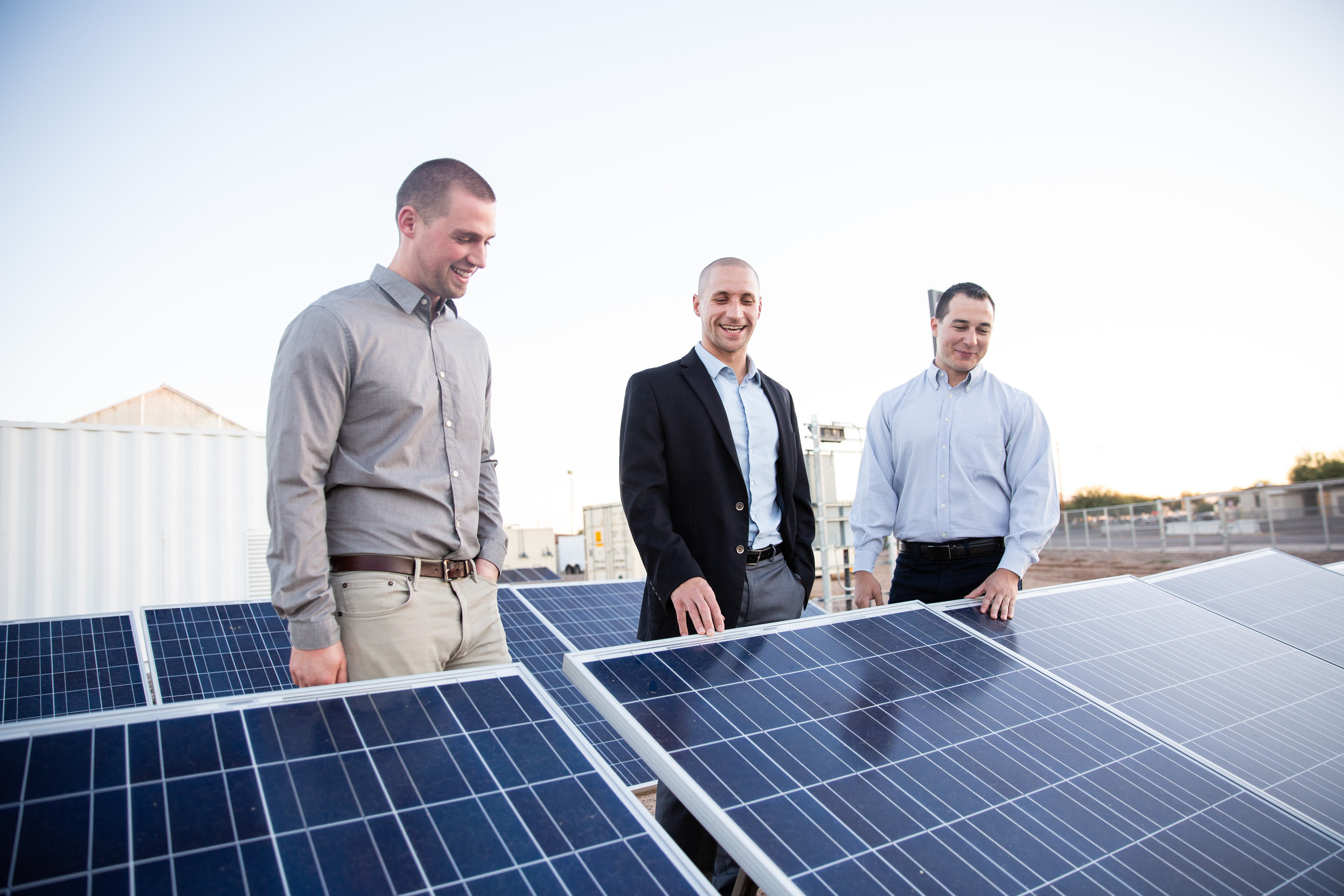 Image of three people looking at solar panels.
