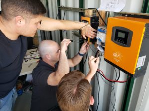Three people working on a microgrid.
